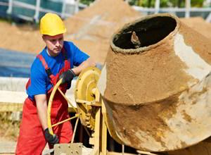 рабочий перемешивает бетон